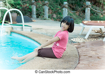Pool woman relaxing sitting in summer dress with legs in pool