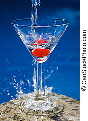 Martini with a cherry in front of a nice blue pool with a splash of water