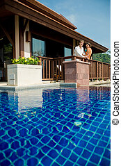 A young attractive couple standing by their pool villa with drinks