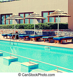 poolside with pool bed and umbrella in luxury resort