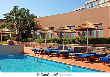 poolside with pool bed and umbrella in summer resort