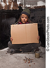 Poor beggar boy on the street with a cardboard sign - Poor...