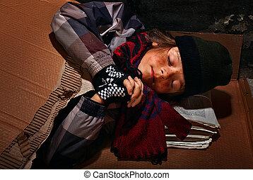 Poor beggar boy preparing to sleep on the street - covered with cardboard box