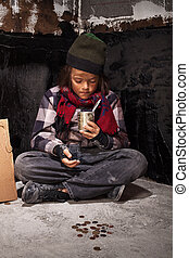Beggar child boy reviews the money he received looking into tin can