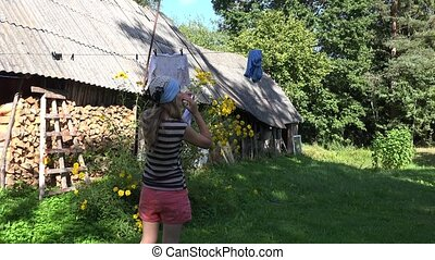 Poor country woman girl hanging laundry towel on clothesline string in rural house yard. 4K
