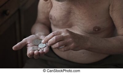 Poor elderly man counting coins in a hand - Homeless person...