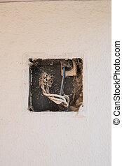 Poor electricity wiring inside a whitewashed wall