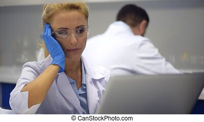Poor female researcher struggling with severe headache at...