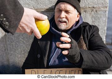 Poor homeless man taking apple