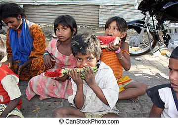 A poor and hungry Indian boy eating a watermelon, his family sitting in the background.