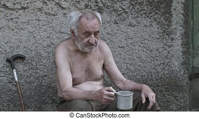 Homeless old man with a cup asking for donation