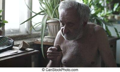 Poor man eating piece of bread - Poor old man eating piece ...