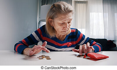 Poor old woman counting coins on the table. Low pension and insufficient funds
