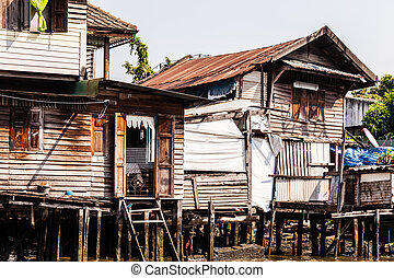 Wooden slums on stilts on the riverside of Chao Praya River in Bangkok, Thailand