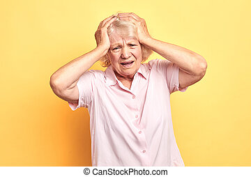 poor senior woman has headache, she touches her head with paalms.