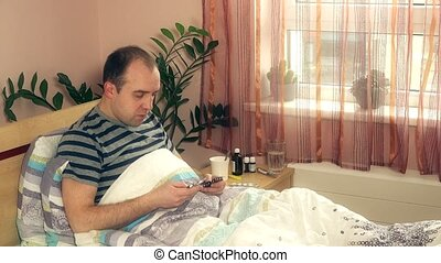 Poor sick man guy choosing pills for treatment in his bedroom