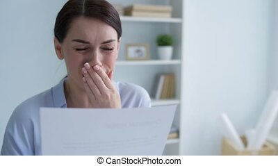 Poor young woman crying after looking at dismissal notice -...