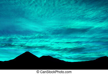 Pop art surreal style turquoise and aqua blue colored sunrise sky over the silhouette of mountains