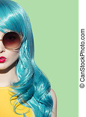 Pop art woman wearing blue curly wig and bright yellow dress. Close uo portrait. Green background. Space for text.