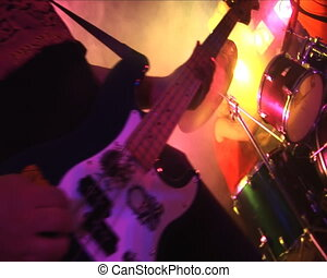 Man play electric guitar in a rock and roll concert.