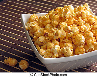 Popcorn - A snack of cheese-flavored popcorn in a small...