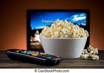 Popcorn and a remote control for the TV background