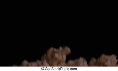 Popcorn bouncing against black background in slow motion