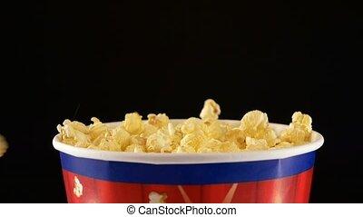Popcorn falling in a bag, on black, 2 pack, slow motion