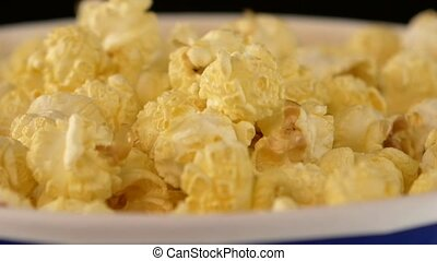 Popcorn falling in a bag, on black, 2 pack, close up, slow motion