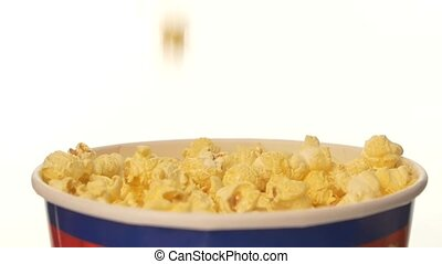 Popcorn falling into a full bag, on white background, 2 pack, close up, slow motion
