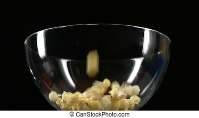 Popcorn falling in glass bowl on black, slow motion