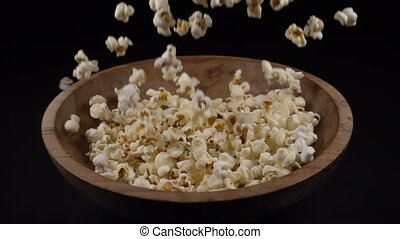 Popcorn falls into a wooden bowl, slow motion