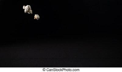 Popcorn falls on a black surface, slow motion