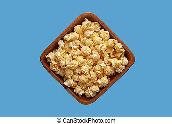 popcorn in a bowl isolated on blue background. Top view