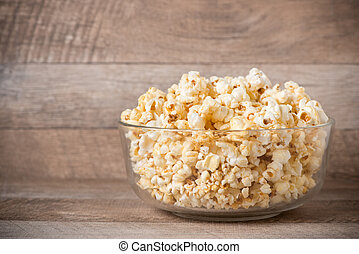 Popcorn in a bowl on the wooden table.