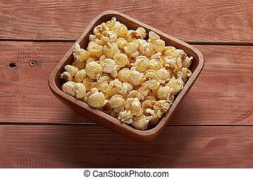 popcorn in a bowl on wooden table. Top view