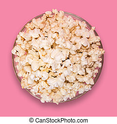 Popcorn in a transparent plate on a pink background.