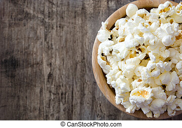 Popcorn in bowl on wooden table. Top view