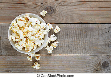 Popcorn in bowl on wooden table top view