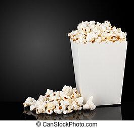 Popcorn in box on black background