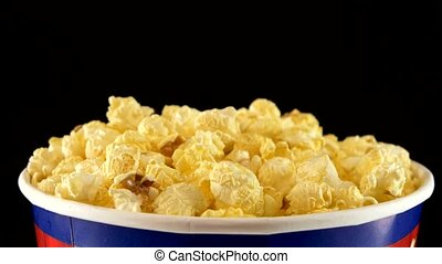 Popcorn in box on black, close up, rotation