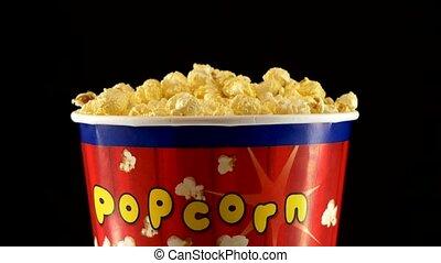 Popcorn in box on black, rotation - Top of popcorn in box on...
