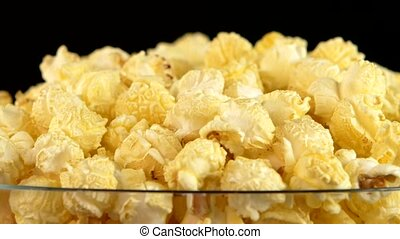 Popcorn in glass bowl on black, rotation, close up