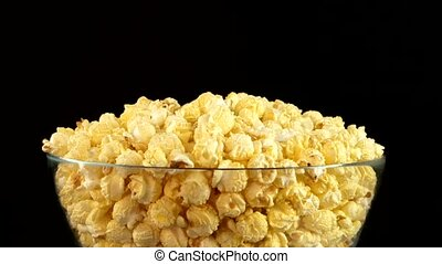 Popcorn in glass bowl on black, rotation