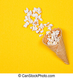 Popcorn in ice cream cones on yellow background. Top view.
