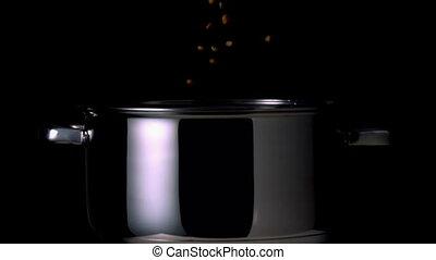 Popcorn kernels falling into pot on black background in slow...