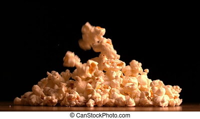 Popcorn pouring on black background in slow motion