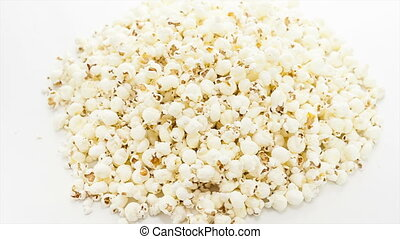 Popcorn rotating on the white table with white seamless...