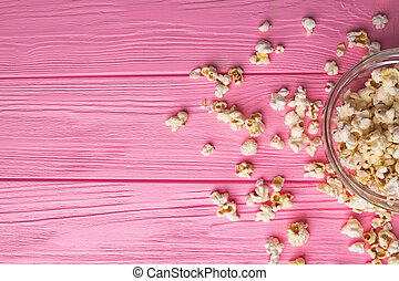Popcorn viewed from above on a pink background.