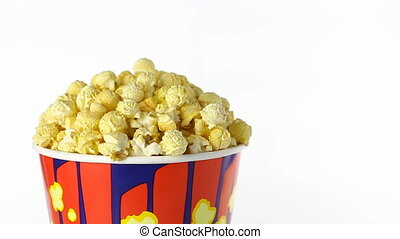 Popcorn with taste of bacon rotates on a white background. Medium shot